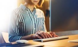 工作在有显示器计算机的在晚上,键入在键盘,女性手的年轻行家经理办公室的女实业家发短信给mes 免版税库存图片
