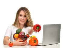 工作在有现代膝上型计算机的书桌的确信的营养师妇女 免版税库存图片