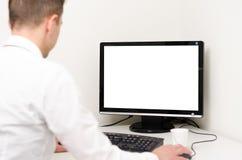 工作在有白色屏幕的一台计算机后的商人 库存照片