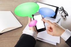 工作在有聊天泡影图标的巧妙的电话的新女实业家 免版税库存图片