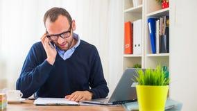 工作在有膝上型计算机和手机的一张书桌上的一个年轻白种人人。 免版税库存照片