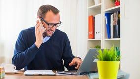 工作在有膝上型计算机和手机的一张书桌上的一个年轻白种人人。 免版税库存图片