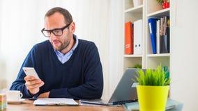 工作在有膝上型计算机和手机的一张书桌上的一个年轻白种人人。 库存图片
