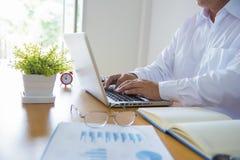 工作在有膝上型计算机的办公室的商人 免版税库存图片