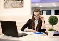 工作在有膝上型计算机的办公室的年轻女商人 库存图片