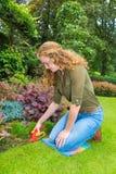 工作在有草剪的庭院里的女孩 库存图片