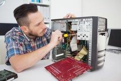 工作在有螺丝刀的残破的控制台的计算机工程师 免版税库存照片