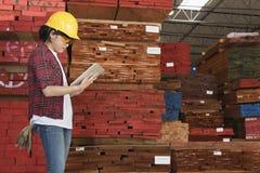 工作在有被堆积的木板条的片剂个人计算机的一名亚裔女性产业工人的侧视图在背景中 免版税库存照片