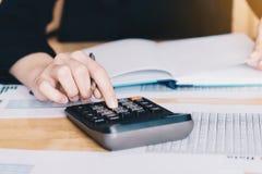工作在有计算器的办公室的女实业家分析计数的财务数据的 库存照片
