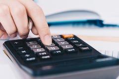 工作在有计算器的办公室的女实业家分析计数的财务数据的 企业财务分析和 免版税库存图片