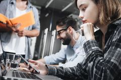 工作在有计算机和膝上型计算机的顶楼办公室的现代coworking的人民照片  工作的概念在数字式设备的 库存图片