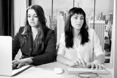 工作在有计算机的办公室的两个女商人在纽约 库存照片