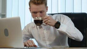 工作在有财政他的膝上型计算机和饮用的咖啡的办公桌的商人围拢由很多文书工作和 股票录像