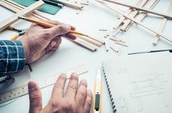 工作在有轻木材料的工作台的男性 图库摄影