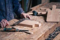 工作在有铅笔和规则的一个木切板的木匠 免版税图库摄影
