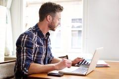 工作在有黏合剂和膝上型计算机认为的书桌的更老的人 免版税库存图片