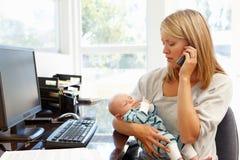 工作在有婴孩的家庭办公室的母亲 免版税库存图片