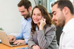 工作在有associ的办公室的年轻可爱的女实业家 免版税库存照片
