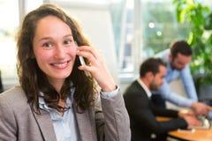 工作在有associ的办公室的年轻可爱的女实业家 免版税库存图片