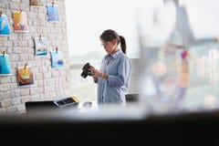 工作在有Dslr照相机和计算机的演播室的摄影师 图库摄影