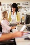 工作在服务台的二名妇女在繁忙的创造性的办公室 库存图片