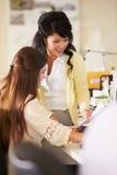 工作在服务台的二名妇女在繁忙的创造性的办公室 免版税库存图片