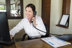 工作在服务台的女性手段接待员 免版税库存照片