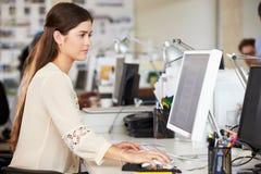 工作在服务台的妇女在繁忙的创造性的办公室 免版税库存图片