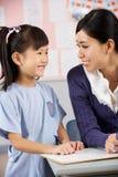 工作在服务台的教师帮助的学员 免版税库存照片
