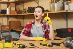 工作在木匠业车间的美丽的白种人年轻棕色头发妇女在桌地方 免版税库存照片