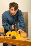 工作在木头的年轻人 库存图片