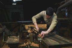工作在木材加工机器的木匠在木匠业商店 男性手Clos 库存图片