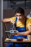 工作在木材加工概念的修理车间的工作者 库存图片