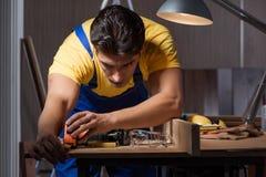 工作在木材加工概念的修理车间的工作者 免版税库存照片