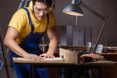 工作在木材加工概念的修理车间的工作者 免版税库存图片