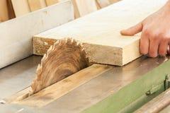 工作在木材加工设备的木匠在木匠业界面 图库摄影
