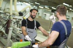 工作在木材车间的英俊的年轻人 免版税图库摄影