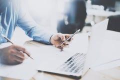 工作在木桌上的商人在现代办公室 使用便携式计算机和智能手机的人 水平,弄脏 免版税图库摄影