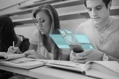 工作在未来派智能手机的被聚焦的大学生 库存照片