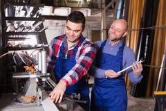 工作在机器的两个人 免版税库存图片
