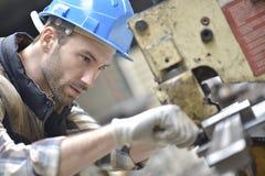 工作在机器的产业工作者在工厂 库存图片