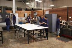工作在机器的工程师在繁忙的金属车间 免版税库存图片