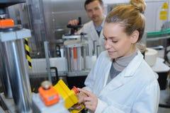 工作在机器的愉快的女性科学家在现代实验室 库存照片