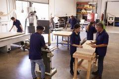 工作在机器的木匠在繁忙的木材加工车间 库存图片