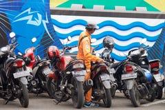 工作在条带,印度尼西亚的一条街道旁边的自行车看守人 库存照片