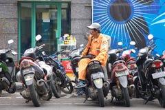 工作在条带,印度尼西亚的一条街道旁边的自行车看守人 免版税库存照片