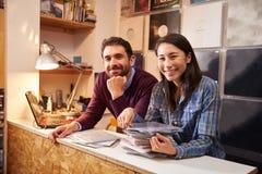 工作在柜台后的男人和妇女在记录商店 免版税库存照片