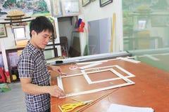 工作在框架的工匠在框架商店 免版税图库摄影