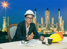 工作在桌上的工程学人反对炼油厂植物美好的照明设备  库存照片