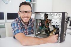 工作在残破的控制台的计算机工程师微笑对照相机 图库摄影